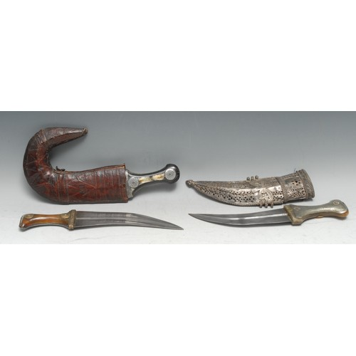 3928 - An Middle Eastern jambiya, 21cm curved blade with central ridge, the horn hilt steel-clad to verso a...