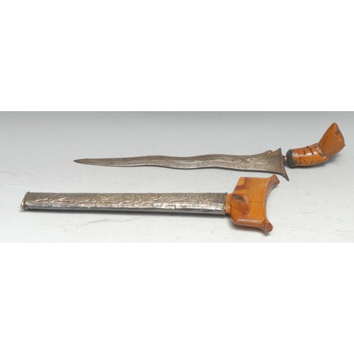3896 - A Malay kris, 26.5cm wavy blade, wooden hulu carved as a stylised lotus, the silver coloured metal c...