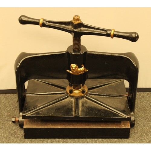 3022 - A 19th century cast iron book press, the frame in relief and picked out in gilt with a recumbent lio...
