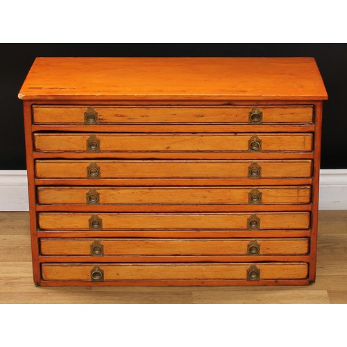 34 - An early 20th century pine table-top specimen or printer's cabinet, oversailing top above seven long...