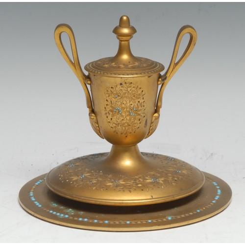 3036 - A 19th century gilt brass urnular inkwell, hinged cover, lofty scroll handles terminating in leafy b...