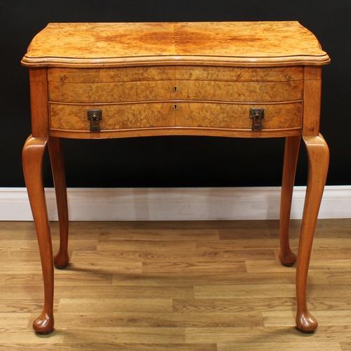 3 - An Art Deco period burr walnut serpentine canteen table, enclosing a George VI service of silver fla...