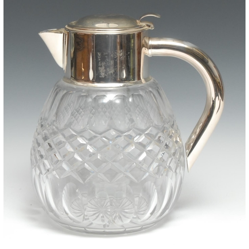 63 - An Edwardian style silver plate mounted clear glass ovoid lemonade jug, hinged cover enclosing a cis...