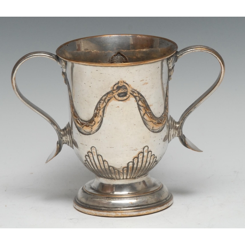 42 - A George III Old Sheffield Plate loving cup, hal-fluted and chased with swags, scroll handles with h...