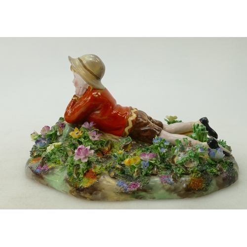 471 - A Crown Staffordshire figurine of a girl lying down, by J T Bailey...
