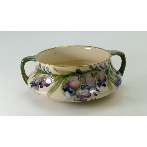 549 - William Moorcroft shallow two handled bowl in the Wisteria design, diameter 19cm (slight wear to gil...