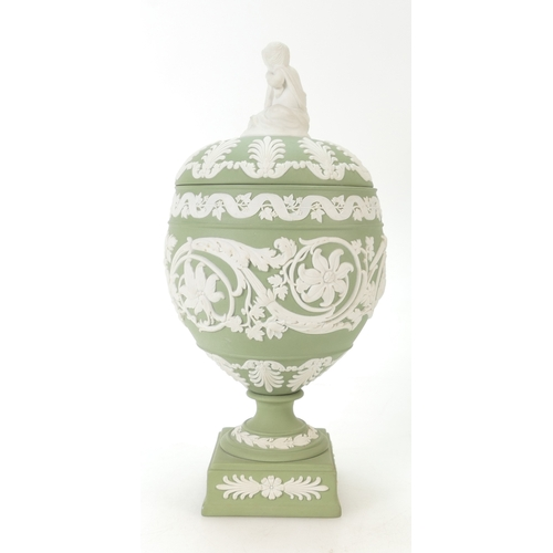 663 - Wedgwood green Jasperware urn and cover decorated all around with scrolling foliage with cupid to li...