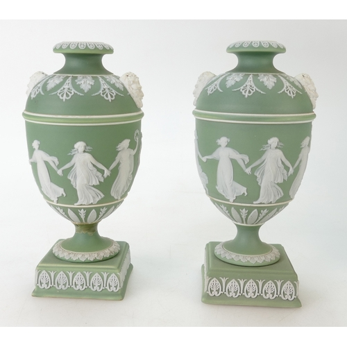 704 - A pair of 19th century Wedgwood green dip Jasperware urns decorated with Dancing Hours Ladies, heigh...