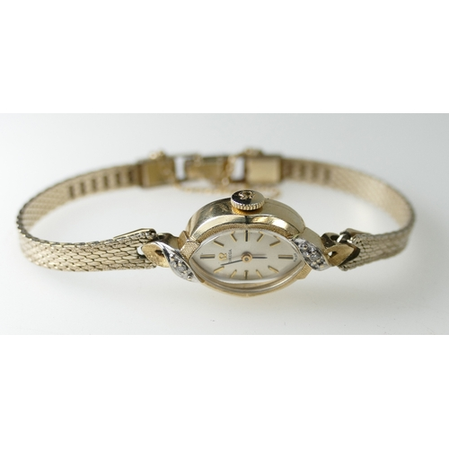 1246 - Ladies 14ct gold Omega Wristwatch set with diamonds on a gold plated bracelet . Ticking order. 12.9g...