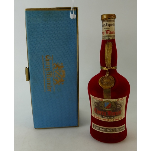 940 - A bottle of Cherry Marnier, a cherry brandy liqueur from Marnier-Lapostolle. This bottle is covered ...