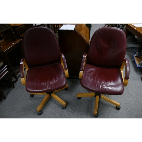 22 - A pair of vintage burgundy leather swivel office arm chairs (2)...