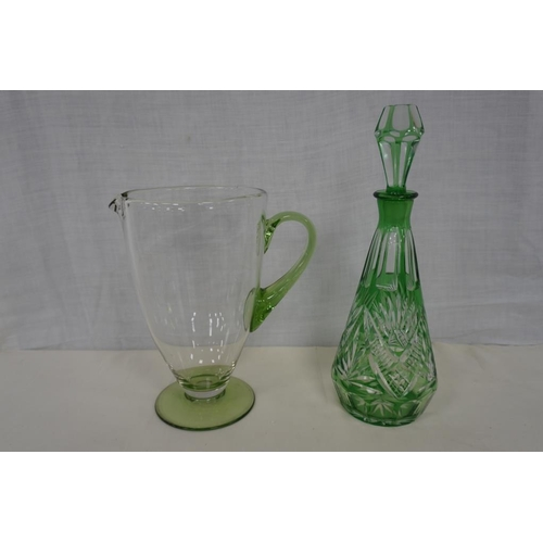 46 - Green cut glass decanter with stopper and hand blown clear glass jug with green glass base and handl...