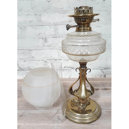 51 - A brass Art Nouveau style oil lamp with glass shade and flu, height 69cm...