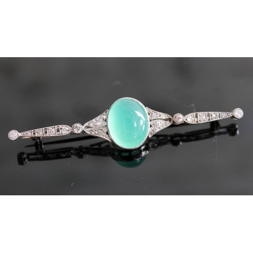103 - An Art Deco diamond encrusted and jade cabochon brooch, the central stone approx. 19mm x 11mm x 6mm,...