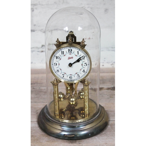 44 - A Schatz torsion clock under glass dome, height 32cm....