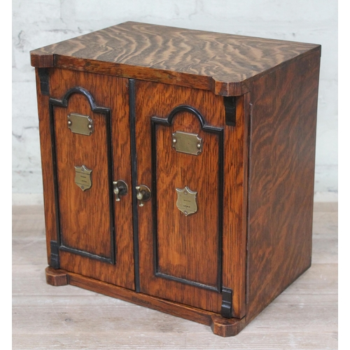 37 - A late 19th century oak smokers cabinet with ebonised arched doors and brass lock, handles and plaqu...