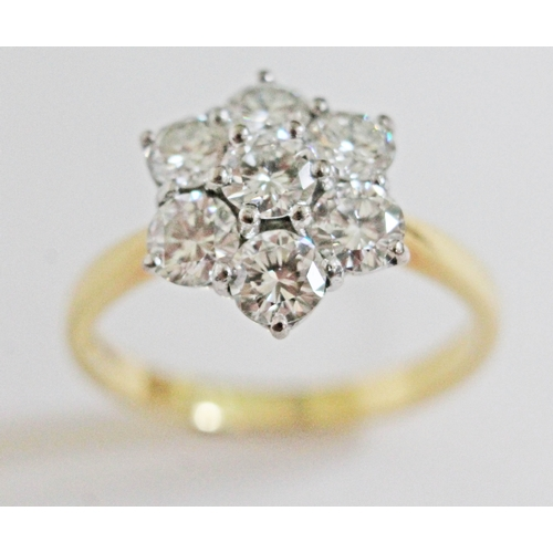 100 - A seven stone diamond cluster ring, the central stone approx. 0.34 carats, the surround six stones a...