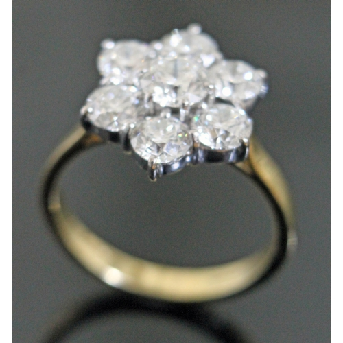 99 - A seven stone diamond ring, the central stone approx. 0.63 carats, surround by six stones approx. 0....