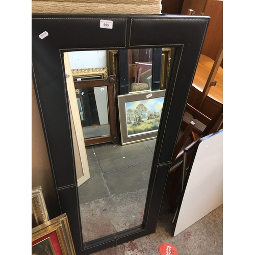 995 - A large mirror with faux leather surround...