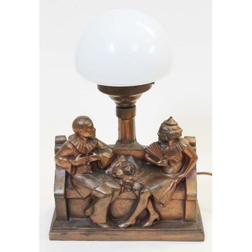 23 - An Art Deco spelter lamp formed as jesters seated on bench with lamppost behind having glass shade, ...