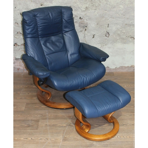 32 - A Norwegian Stressless blue leather and laminate wood reclining armchair with matching stool....