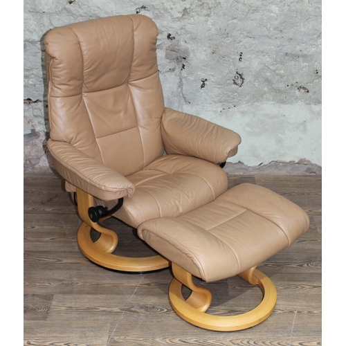40 - A Norwegian Ekornes Stressless tan leather and light laminate reclining armchair and matching stool....