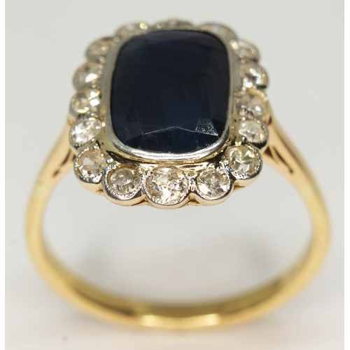 102 - A sapphire and diamond ring, the central rectangular cut stone approx. 5.43ct, the surrounding stone...