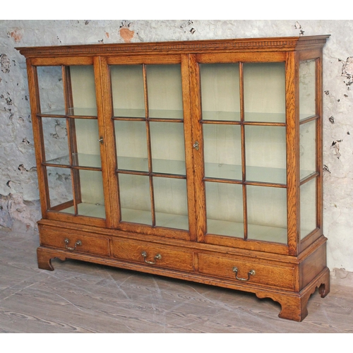 12 - An aged oak glazed bookcase, dentilated cornice, panelled glass front and sides above three lower dr...