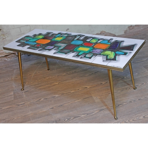 20 - A retro abstract tile top coffee table with spindle legs, length 103.5cm....