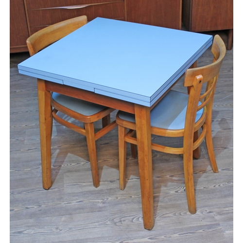 23 - A 1950s blue formica drawer leaf kitchen table and two chairs....