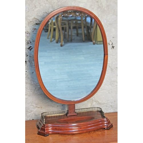 29 - An Edwardian mahogany oval toilet mirror with lower pierced brass gallery rail, height 73cm....