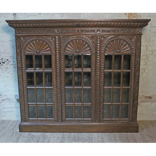3 - A late Victorian large carved oak glazed bookcase having gadrooned cornice, acanthus frieze, bevelle...