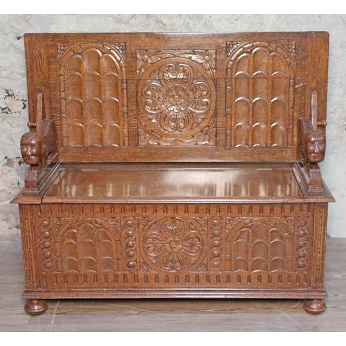 8 - A carved oak monk's bench circa 1920, width 122cm, depth 53.5cm & height 71cm....