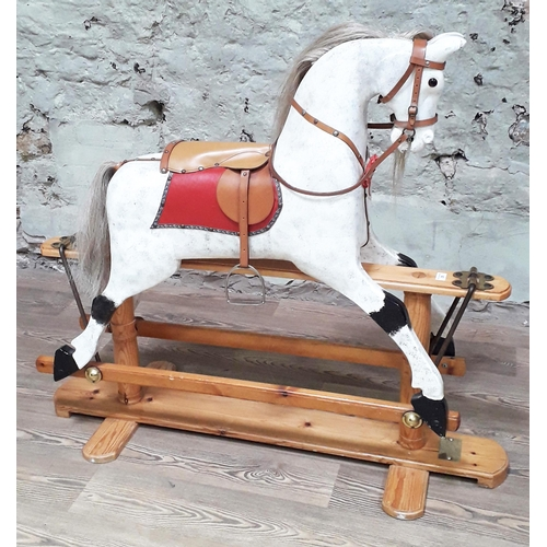 26 - A contemporary painted carved wooden rocking horse on pine base with brass plaque inscribed  'Made b...