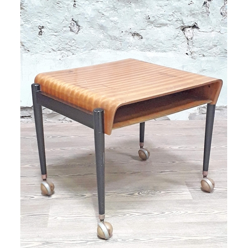 27 - A 1950s bent plywood and black magazine table on Shepherds castors, width 51cm, depth 60cm & height ...