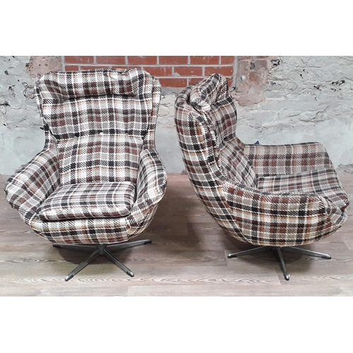10 - A pair of retro swivel egg chairs with checked upholstery. (This item may not comply with the Furnit...