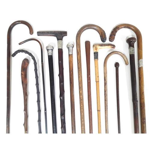 6 - A group of twelve various walking canes and a leather riding crop, various woods, mounts and handles...
