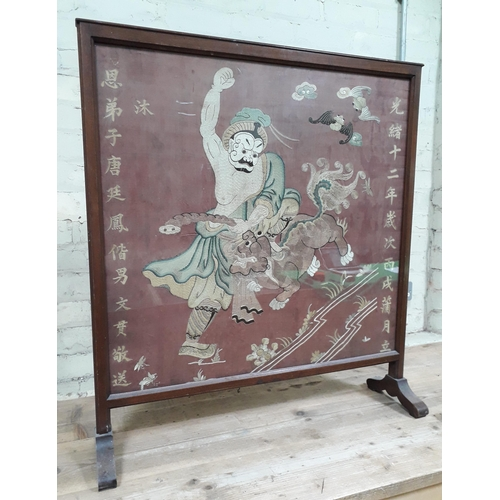 9 - A Chinese embroidered panel depicting a warrior fighting a dragon with two bats above and characters...