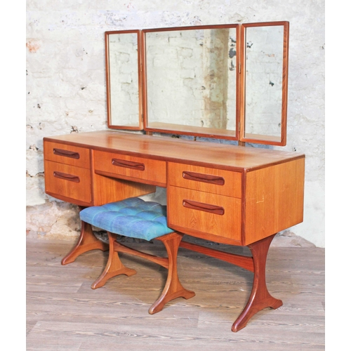 16 - A G-Plan teak dressing table with triple mirror and stool, length 137cm, depth 50cm & height 131cm....