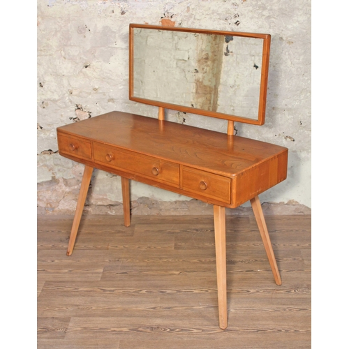 2 - An Ercol Blonde elm and beech dressing table, mirror back, three drawers with splayed legs, width 11...