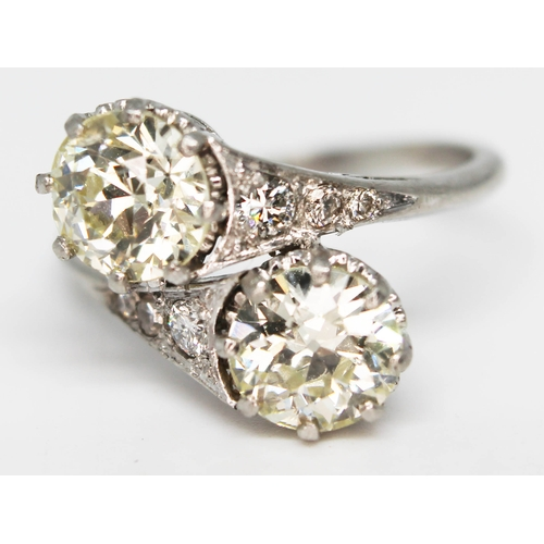 207 - A diamond cross over ring, the two stones weighing approx. 1.12 & 1 carat, diamond set shoulders, pl...