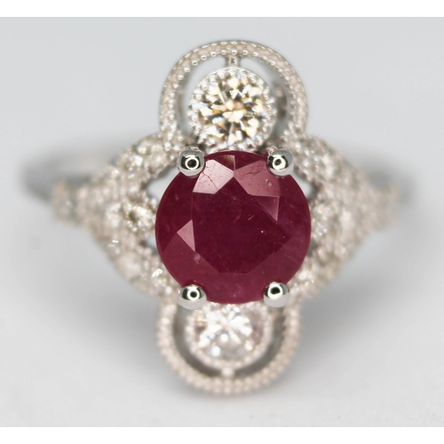 158 - An 18ct white gold ruby and diamond cluster ring featuring a round brilliant cut ruby approx. 0.98ct...