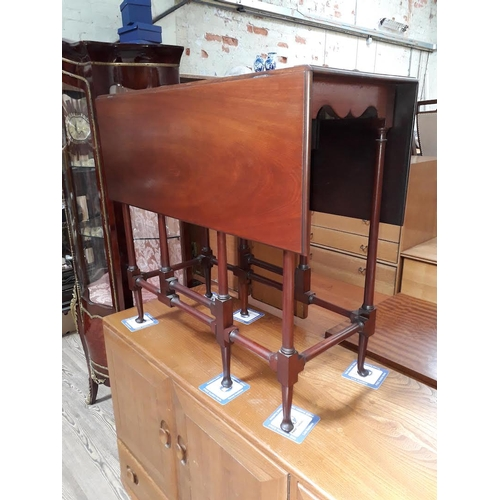 26 - An Edwardian mahogany Sutherland table with turned stretchers....