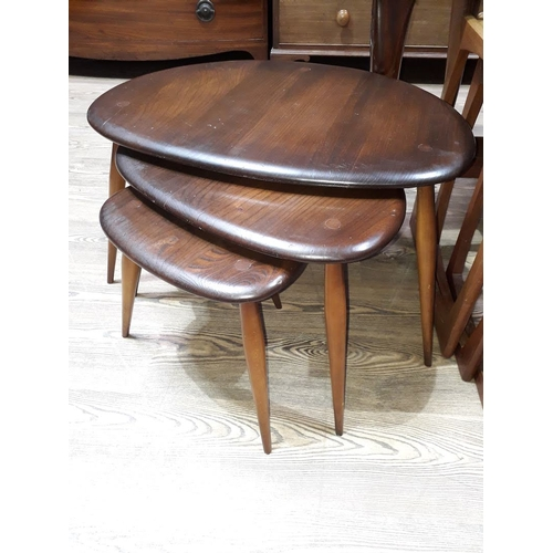 29 - A set of three Ercol elm and beech nest of tables, blue label number 354 circa 1957....