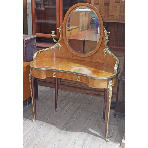 65 - A French kidney shaped amboyna and ormolu mounted dressing table, early 20th century with oval swing...