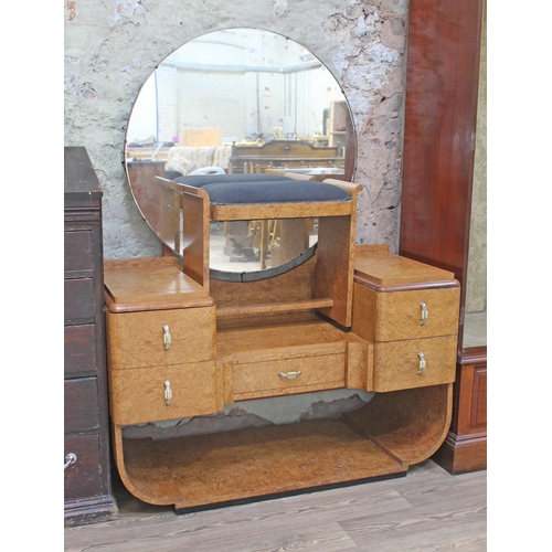 17 - An Art Deco burr walnut dressing table and stool in the manner of Epstein with large round mirror, s...