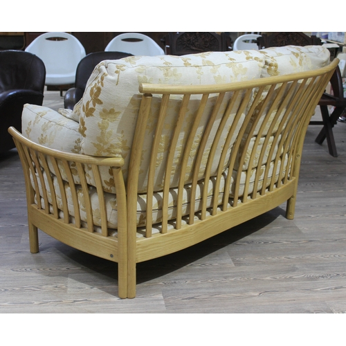 18 - An Ercol Renaissance light ash settee with green and gold floral upholstery....