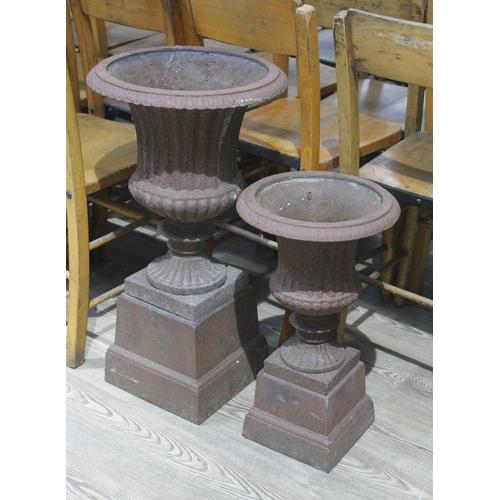 27 - Two cast iron garden urns, heights 50cm & 67cm....