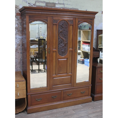 28 - A late Victorian mahogany wardrobe with flared cornice top, central panel with carved dragon, two do...