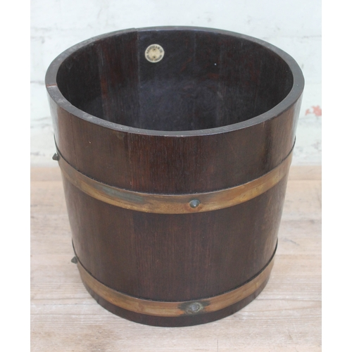 37 - An R.A. Lister brass bound oak jardiniere, height 28cm....